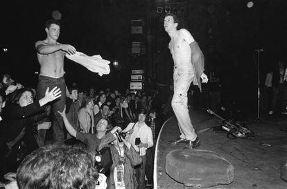 Joe Strummer trocando a camiseta com alguém do público em um show do The Clash em 1977.