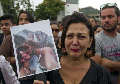 Uma mulher mostra uma foto da ex-miss e seu marido.