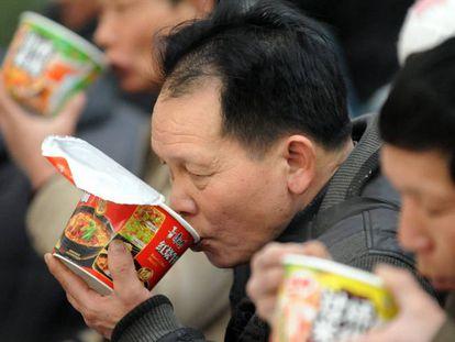 Vários passageiros comem macarrão instantâneo na estação de trem de Shenyang.