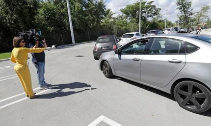Repórter entrevista a distância um motorista na fila de um 'drive-through' de testes da Covid-19, nesta sexta-feira, no Doris Ison Health Center em Miami.