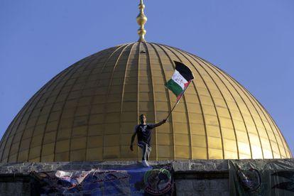 Homem tremula a bandeira palestina em Al Aqsa, Jerusalém, durante as celebrações do Eid al-Fitr, nesta quinta-feira.