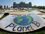 Activists place thousands of protest placards in front of the Reichstag building, home of the german federal parliament, Bundestag, during a protest rally of the 'Fridays for Future' movement in Berlin, Germany, Friday, April 24, 2020. Youth groups are staging a long-planned global climate demonstration online Friday because of restrictions on public protests during the coronavirus pandemic. (AP Photo/Michael Sohn)