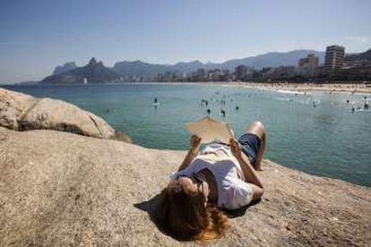 O estudante Victor Caplin lê um livro nas pedras do Arpoador, na praia de Ipanema (Rio).