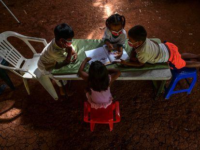 Crianças indígenas embera consultam um livro durante as aulas em sua comunidade em março de 2021 no Panamá.