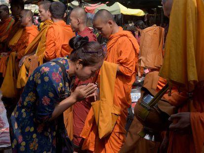 Uma mulher diante de monges budistas no Camboja.