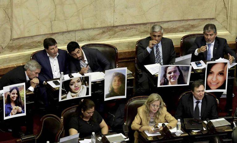 Deputados argentinos mostram fotos de mulheres assassinadas.