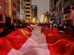 Supporters of Peru's presidential candidate Pedro Castillo carry an oversized Peruvian flag on a street a day after a run-off election, in Lima, Peru June 7, 2021. REUTERS/Alessandro Cinque