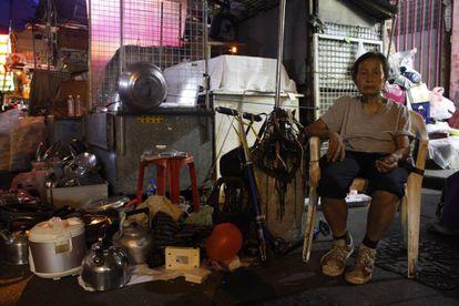 A senhora Chan, de 79 anos, em seu posto ilegal, onde também vive, no bairro de Sham Shui Po.