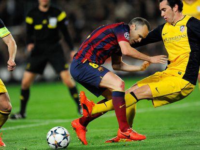 Iniesta e Godín lutam pela bola.