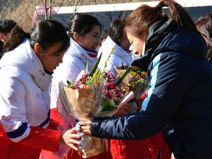 Jogadora sul-coreana entrega flores para a colega norte-coreana, nesta quinta-feira.