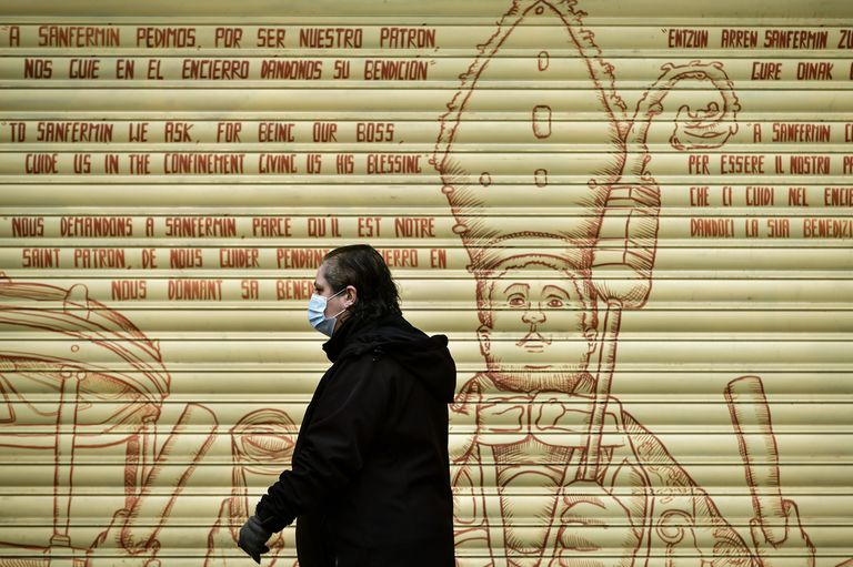 A woman wearing a face mask walks in front of graffiti depicting Saint Fermin, with writing in many different languages asking for blessings, in Pamplona, northern Spain, Wednesday, March 18, 2020. Spain will mobilize 200 billion euros or the equivalent to one fifth of the country's annual output in loans, credit guarantees and subsidies for workers and vulnerable citizens, Prime Minister Pedro Sanchez announced Tuesday. For most people, the new coronavirus causes only mild or moderate symptoms. For some, it can cause more severe illness, especially in older adults and people with existing health problems. (AP Photo/Alvaro Barrientos)