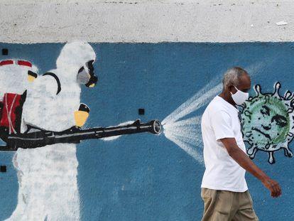 Um homem usando máscara de proteção passa por um mural com referência à pandemia no Rio de Janeiro, em 12 de junho.