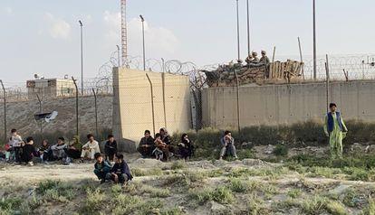 Um grupo de pessoas aguarda nos acessos do aeroporto de Cabul.