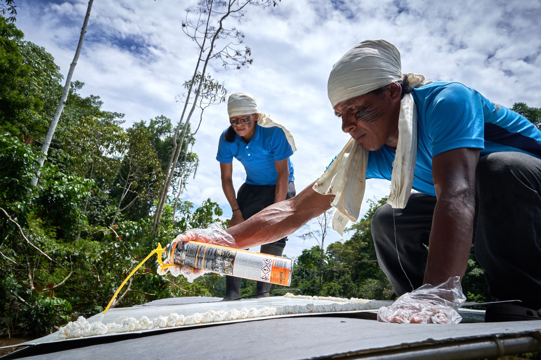 Uma equipe de técnicos indígenas instala os painéis solares no teto do novo barco.