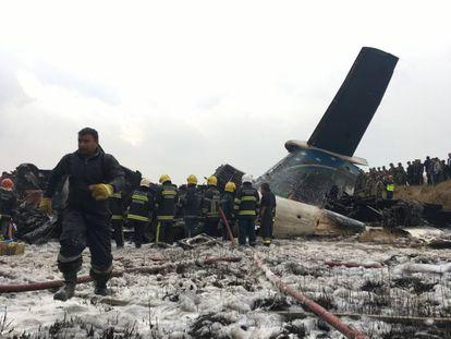 Equipe de resgate junto ao avião procedente de Bangladesh que caiu no Nepal.