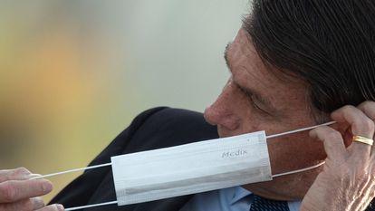 O presidente Jair Bolsonaro coloca uma máscara durante cerimônia oficial no Palácio da Alvorada, em 9 de junho de 2020.