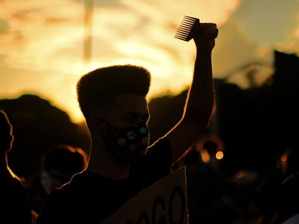"A protester takes part in a demonstration against racism and against Brazilian President Jair Bolsonaro in Rio de Janeiro, Brazil, on June 7, 2020 amid the COVID-19 novel coronavirus pandemic. - Brazilians took to the streets for rival demonstrations on Sunday for and against President Jair Bolsonaro, who has been widely criticized over his response to the coronavirus pandemic. Demonstrators, many dressed in black and wearing face masks, held banners saying: ""Everyone for democracy"", ""Against racism and fascism"" and ""Terrorism is the government's policy of extermination."" (Photo by Carl DE SOUZA / AFP)"
