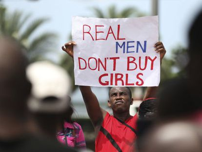 """Um homem levanta um cartaz onde se lê """"os homens de verdade não compram meninas"""", em um protesto em Lagos contra Boko Haram."""