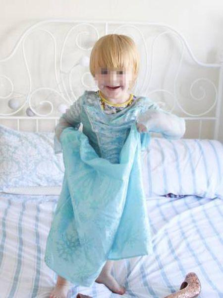 Noah brincando na cama de seus pais com sua roupa favorita, de princesa Elsa.