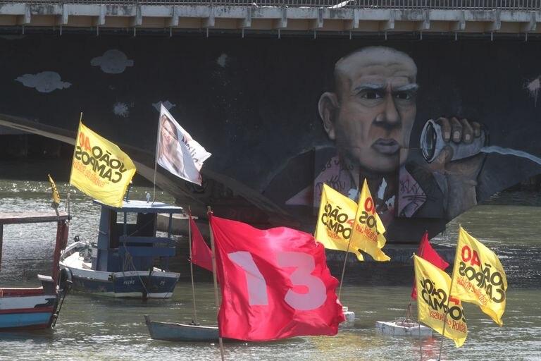 Barcos com bandeiras de políticos na bacia do Pina, ao lado de favela de palafitas.