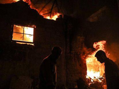 Personas caminan frente a edificios en llamas en Duma (Siria).