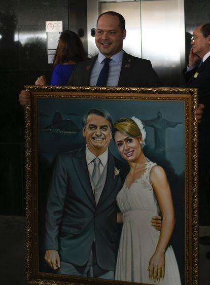 Heitor Freire segura uma pintura de Bolsonaro e sua esposa em fevereiro de 2019.