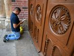 A man prays at a door of the closed Basilica of the Lord of Miracles in Buga, Colombia, on March 17, 2020 after it was closed as a preventive measure against the spread of the new coronavirus, COVID-19. - The Basilica of the Lord of Miracles is one of the most important and most visited religious shrines in the country. (Photo by Luis ROBAYO / AFP)