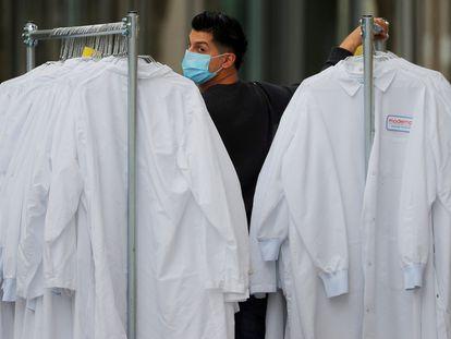 Funcionário leva trajes de proteção à sede da Moderna Therapeutics, em Cambridge (EUA), nesta segunda-feira.