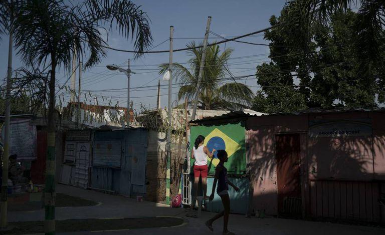 Moradora do Complexo do Alemão, no Rio de Janeiro, pinta a bandeira do Brasil numa parede.