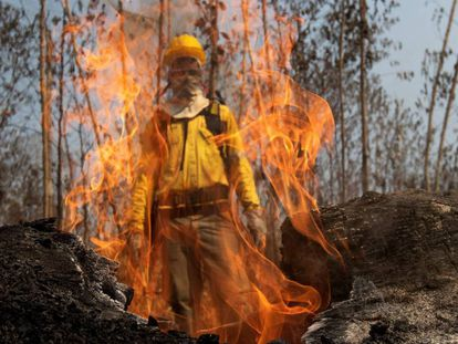 Bombeiro atrás de chamas durante o combate aos incêndios na floresta amazônica, próximo de Porto Velho.