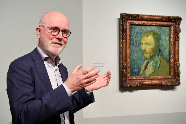 O pesquisador Louis van Tilborgh ao lado do retrato de Vincent van Gogh em Amsterdã.