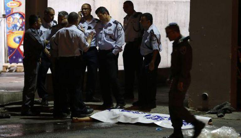 Policiais israelenses junto ao corpo do agressor/ YEHUDA PERETZ (AFP)