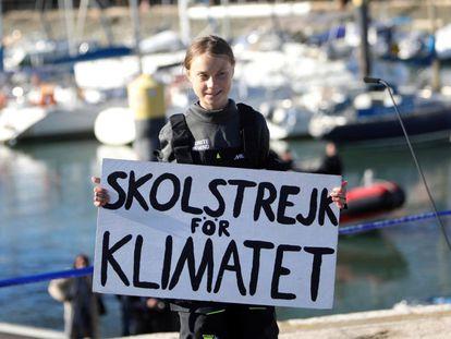 """Greta Thunberg segura um cartaz onde se pode ler """"Skolstrejk för klimatet"""" (en sueco, greve escolar pelo clima), em sua chegada a Lisboa."""