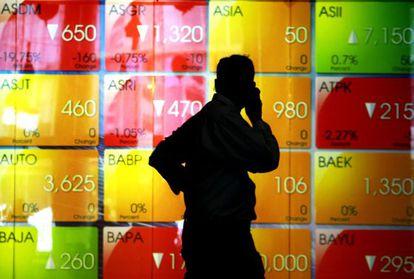 Um homem fala ao telefone em frente a uma tela com os valores do índice indonésio IDX, em Jacarta.