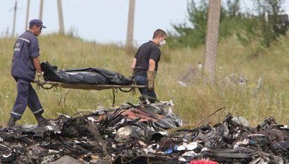 Dois ucranianos levam os restos das vítimas do voo MH17.