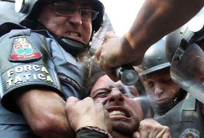 Policial dispara spray de pimenta em manifestante imobilizado.