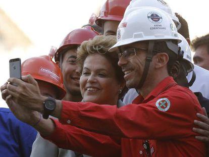 Dilma posa para fotos com trabalhador da Arena Corinthians.