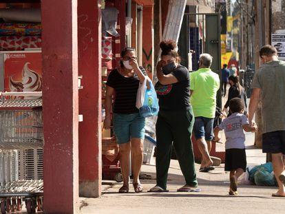 Pessoas utilizando máscaras fazem compras neste sábado em  uma rua de Brasília.