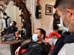 A client wearing a protective face mask gets his beard trimmed at a barber's salon in Bordeaux, southwestern France, on May 11, 2020 on the first day of France's easing of lockdown measures in place for 55 days to curb the spread of the COVID-19 pandemic, caused by the novel coronavirus. (Photo by GEORGES GOBET / AFP)