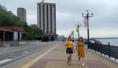 Duas mulheres caminham ao longo do passeio marítimo do rio Amur em Khabarovsk na sexta-feira.