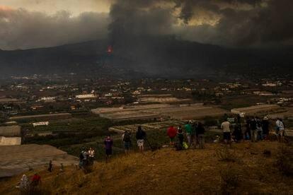 Um grupo de curiosos contempla a erupção do vulcão em La Laguna, na terça-feira.