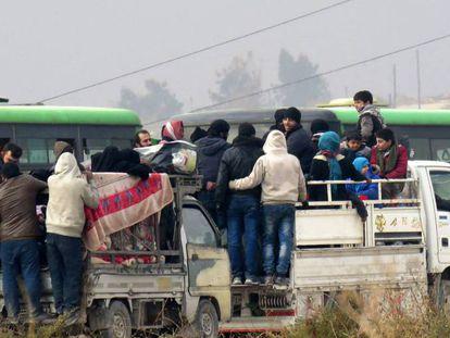 Um grupo de sírios abandona, na sexta-feira, os bairros rebeldes de Aleppo.