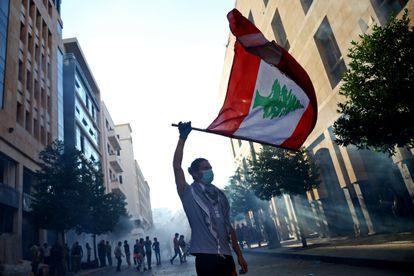 Manifestante carrega bandeira do Líbano em protesto nesta segunda. Pressão das ruas levou à renúncia do Governo