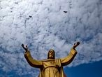 Birds fly over a statue of Jesus Christ outside a church on the eve of Christmas in Gauhati, India, Thursday, Dec. 24, 2020. Though Hindus and Muslims comprise a majority of the population in India, Christmas is a national holiday celebrated with much fanfare. (AP Photo/Anupam Nath)