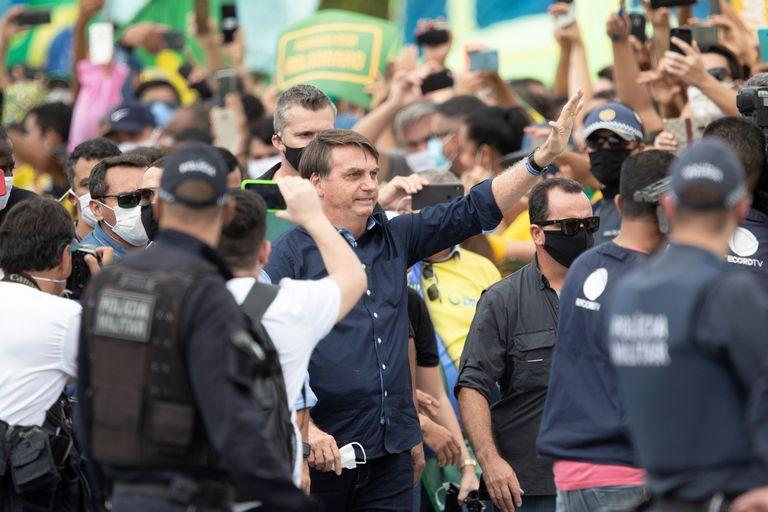Bolsonaro rodeado de apoiadores em frente ao Palácio do Planalto neste domingo.