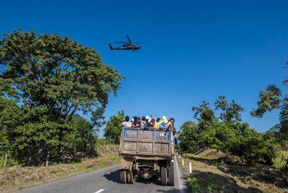 Um grupo de hondurenhos é levado em um caminhão de materiais enquanto um helicóptero da polícia federal mexicana vigia seu trajeto.