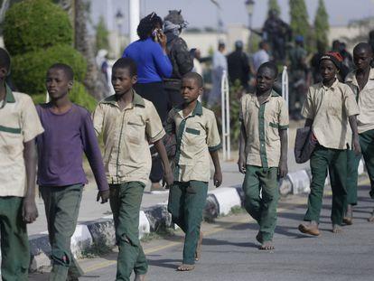 Alguns dos estudantes nigerianos que ficaram seis dias sequestrados caminham em fila em direção a um prédio do Governo, após serem libertados, nesta sexta-feira, na cidade de Katsina.