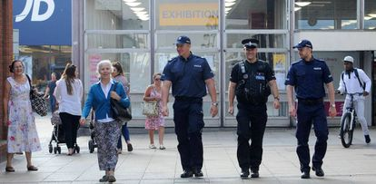 Policiais poloneses fazem patrulha com um agente britânico, após assassinato de um jovem polonês.