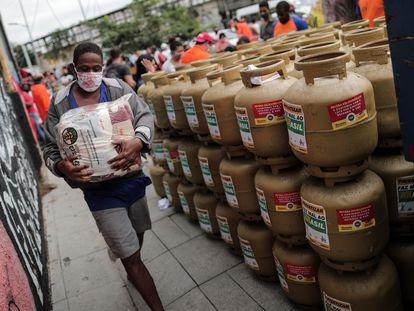 Homem carrega um pacote de alimentos que foi doado por um grupo de pessoas em uma campanha promovida por uma federação de trabalhadores no Rio de Janeiro, que vendeu gás pela metade do preço.