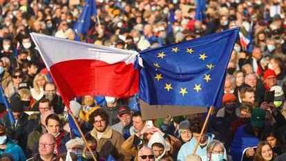 Vários manifestantes erguem bandeiras da Polôniaeda UE, em uma marcha no domingo emCracóvia.